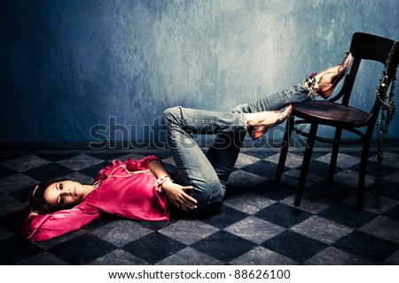 woman in oriental shirt and shoes lie on floor - stock photo