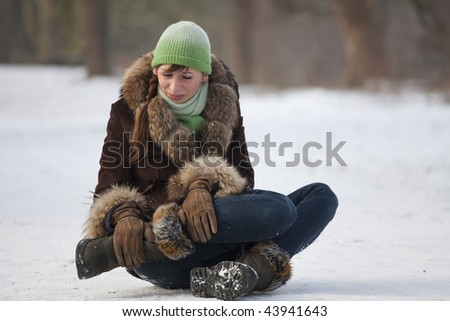 woman in pain holds her leg after slipping on snowy road - stock photo