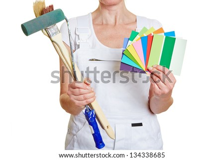 Woman in painter outfit holding brushes and color samples - stock photo