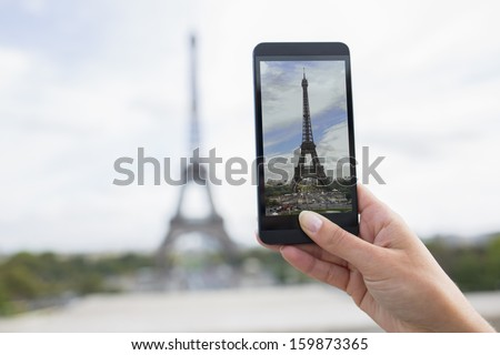 Woman in Paris taking pictures in front of Eiffel Tower, Cell phone - stock photo
