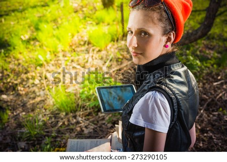 Woman in park outdoor with tablet and paper book deciding what to use