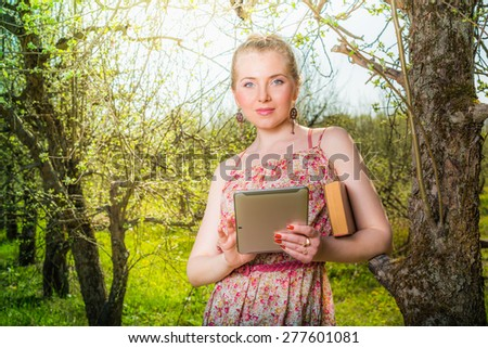 Woman in park outdoor with tablet and paper book deciding what to use - stock photo