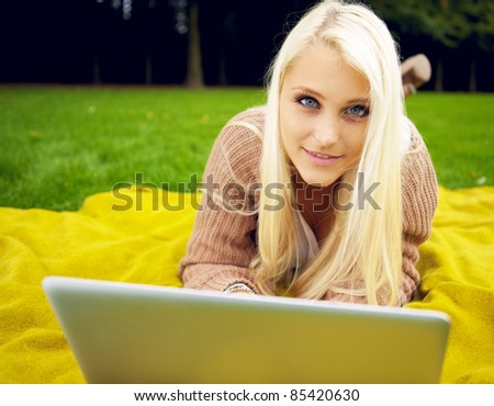 Woman in park with laptop relaxing - stock photo