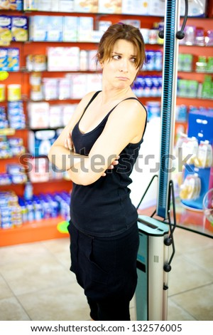 Woman in pharmacy depressed about how much she weights, anorexia problem - stock photo