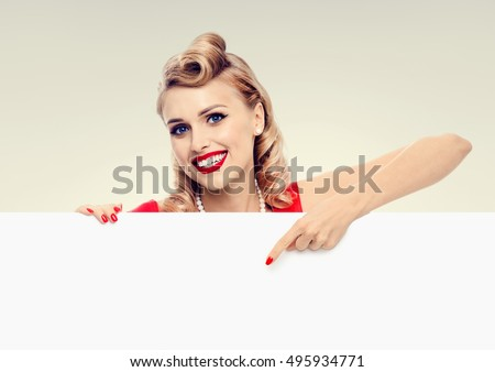 Woman in pin-up style dress, showing blank signboard with copyspace area for advertising slogan or text message. Caucasian blond model posing in retro fashion and vintage concept studio shoot.