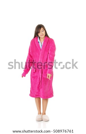 Woman in pink bathrobe pointing down.
