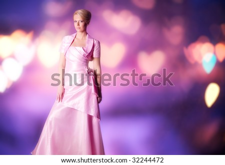 Woman in pink dress on abstract blurry background. - stock photo