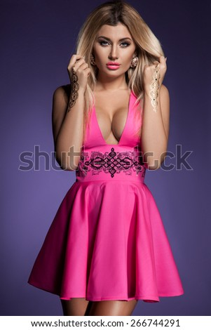 woman in pink dress on violet background - stock photo