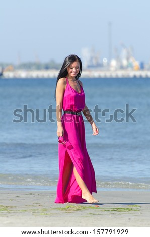 Woman in pink dress walking on the beach - stock photo