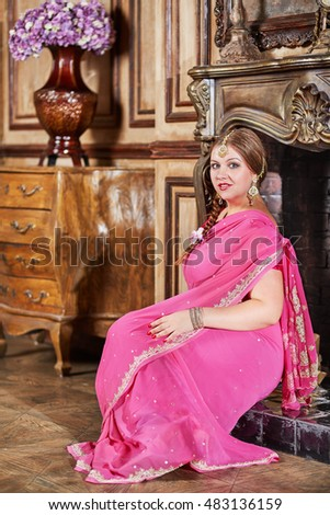 Woman in pink dress with decorations on head sits at fireplace in room.
