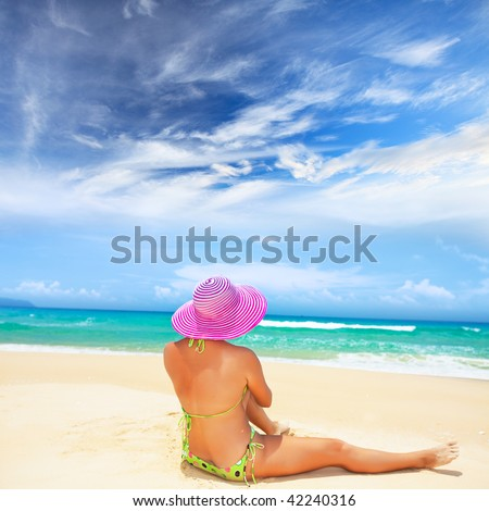 Woman in pink hat is sitting on the beach