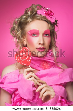 Woman in pink. Portrait of young lady in creative image and with lollipop.