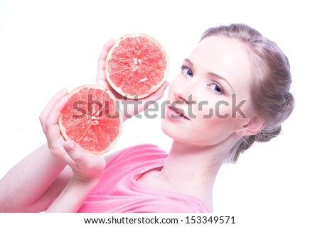 Woman in pink shirt with grapefruit in her hands.