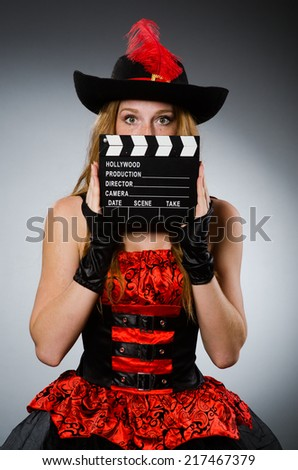 Woman in pirate costume with movie board - stock photo