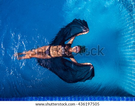 Woman in pool in black dress - stock photo