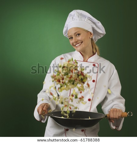 woman in professional cook's uniform cooking vegetables motion blur