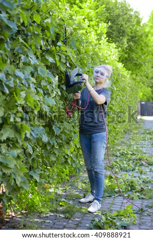 Woman  in protective glasses trimming hedges with electric hedge trimmer tool. Gardening concept