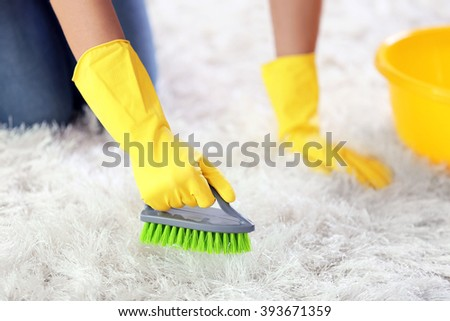 Woman in protective glove cleaning carpet with brush