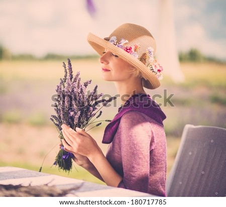 Woman in purple dress and hat behind table in lavender field  - stock photo