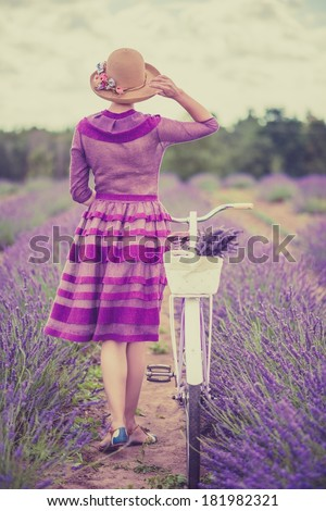 Woman in purple dress and hat with retro bicycle in lavender field - stock photo