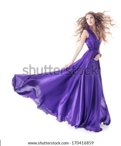 Woman in purple silk waving dress with long hairs walking over isolated white background  - stock photo