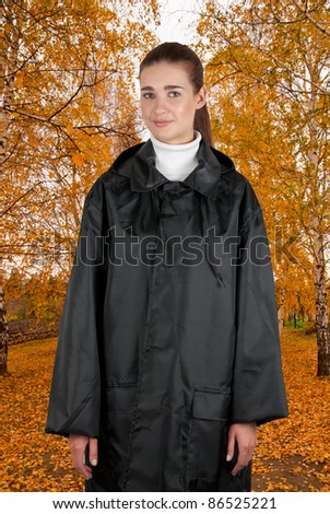 woman in rain coat walking at autumn forest