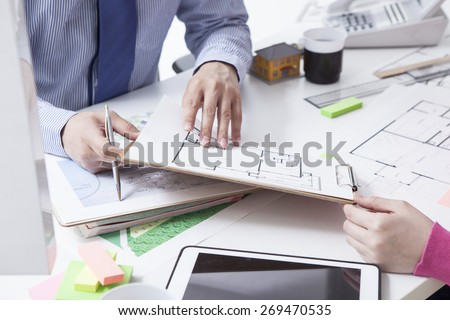 Woman in real-estate agency talking to construction planner  - stock photo