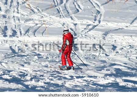 Woman in red and ski traces on snow - stock photo