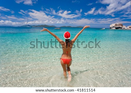 woman in red bikini on tropical beach with merry christmas holiday hat