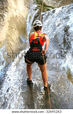 Woman in red climbing a waterfal - outdoor extreme - stock photo