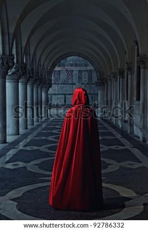 Woman in red cloak walking away - stock photo