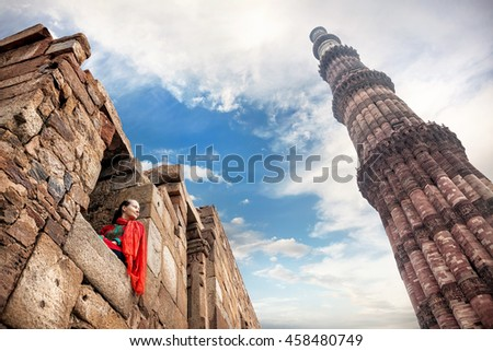 Woman in red costume sitting in the window and looking at Qutub Minar tower in Old Delhi, India