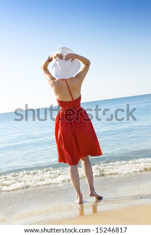 woman in red dress  and white hat looking at the horizon over blue sea - stock photo