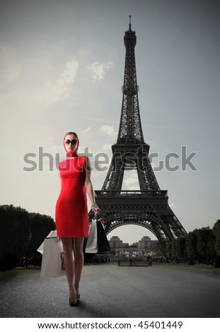 Woman in red dress carrying some shopping bags with the Eiffel tower on the background - stock photo