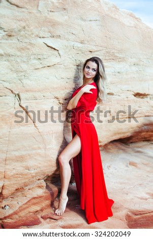 Woman in red dress  on the background of sands career - stock photo