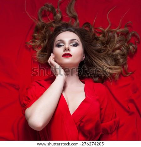 Woman in red dress posing with waving fabric, the girl touches face - stock photo