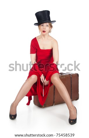 Woman in red dress sitting on a suitcase - stock photo