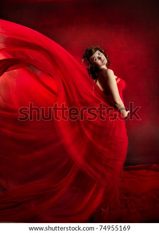 Woman in red dress waving flying on wind flow, Fashion Beauty Model Posing in Flowing Cloth