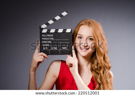 Woman in red dress with movie board - stock photo
