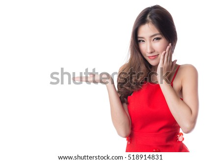 Woman in red dress with open palm hand gesturing, presenting, business and celebration concepts,  isolated on white background