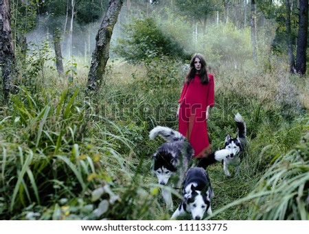woman in red dress with tree wolfs in forest - stock photo