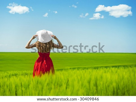 woman in red enjoying nature in a green field - stock photo