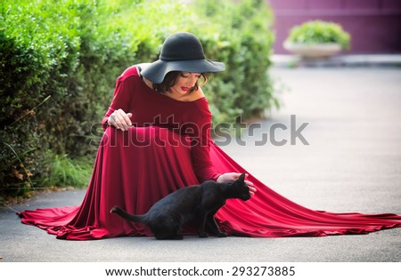 Woman in red evening dress with a black cat - stock photo