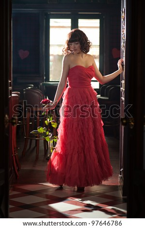 Woman in red evening dress with the rose - stock photo