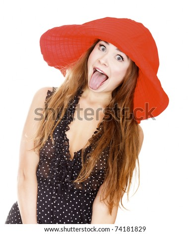Woman in red hat posing against white background and showing her tongue. - stock photo