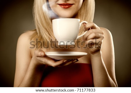 woman in red holding cup and smiles - stock photo