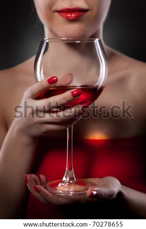 woman in red holding wine glass and smiles - stock photo