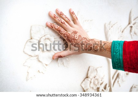 Woman in red Indian costume touching white marble wall with floral pattern by hand in henna painting in Taj Mahal in Agra, Uttar Pradesh, India - stock photo