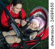 Woman in red jacket with baby buggy outdoors - stock photo