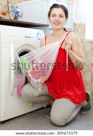 woman  in red  loading the washing machine with laundry bag in kitchen